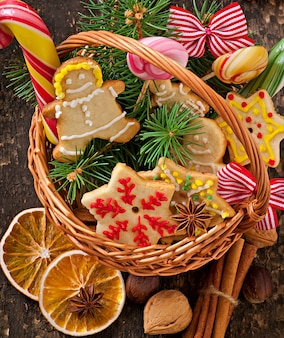 Christmas gingerbread cookies and lollipops in a basket on old wooden background