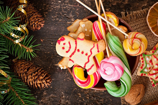 Christmas gingerbread cookies and lollipops  on old wooden background