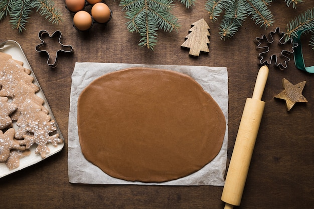 Christmas gingerbread cookies and raw dough with copy space on wooden space