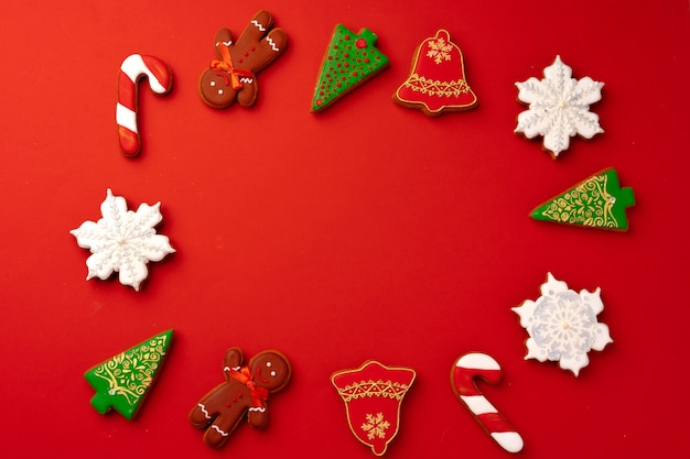 Christmas gingerbread cookies on red background top view, copy space