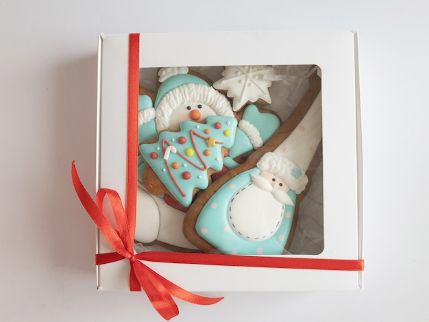 Christmas gingerbread cookies sugar glazed in white gift box with red ribbon