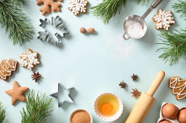 밝은 파란색 배경에서 요리 재료로 크리스마스 진저 쿠키. 즐거운 성탄절 보내시고 새해 복 많이 받으세요. 공간 복사