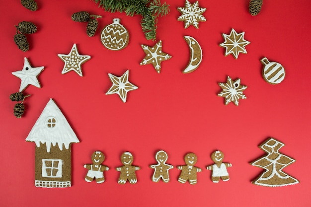 Christmas gingerbread cookies with new year decorations on red background. holidays, christmas, dessert, new year food, design elements concept