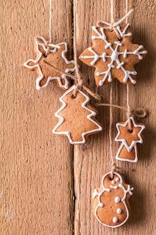 Рождественские пряники, висящие на деревянной поверхности