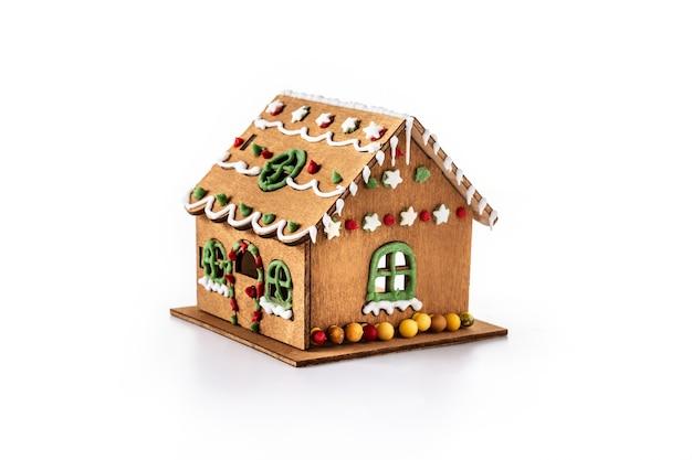 白い背景で隔離のキャンディーと釉薬で飾られたクリスマスジンジャーブレッドの家