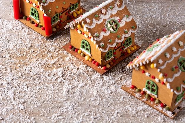 木製のテーブルにキャンディーと釉薬で飾られたクリスマスジンジャーブレッドハウス