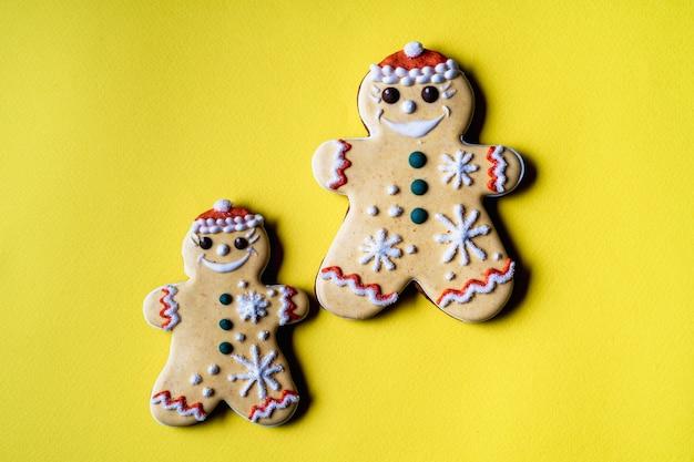 黄色の背景に天使の形をしたクリスマスジンジャーブレッド、フラットレイ。