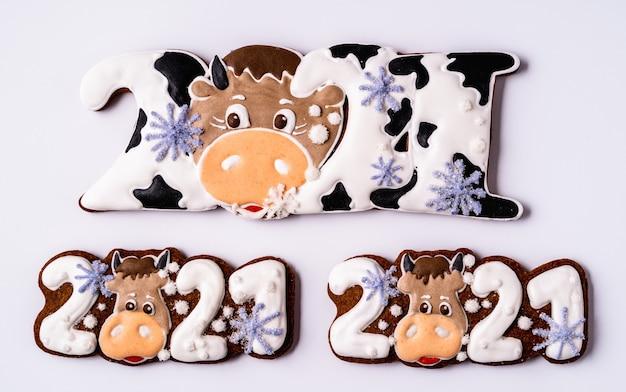 白い背景の上の雄牛の形をしたクリスマスのジンジャーブレッド、フラットレイ。