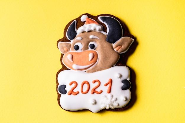 黄色の背景に雄牛の形をしたクリスマスジンジャーブレッド、フラットレイ、クローズアップ。