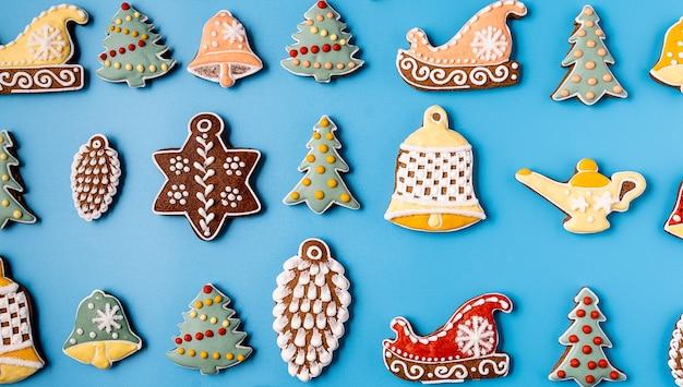 Рождественские пряники на синем фоне. снежинка, ель, звезда, конус, звезда, форма колокола.