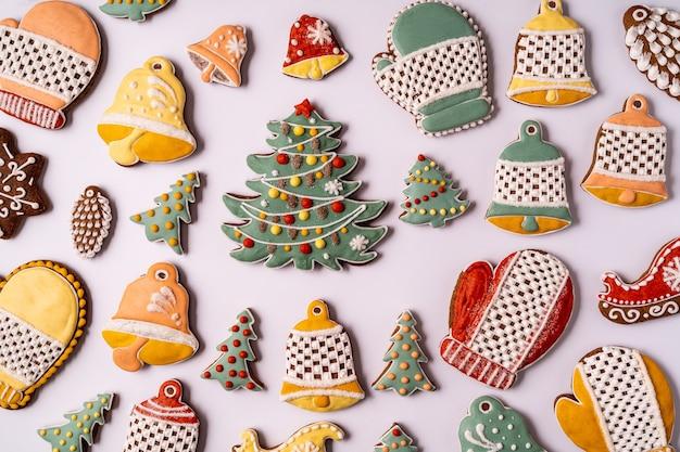 Рождественские пряники на сером фоне. снежинка, ель, звезда, конус, звезда, форма колокола