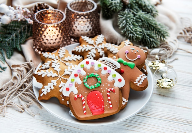 Christmas gingerbread in the plate and candles on white wooden background. top view.
