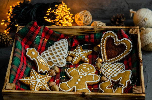 Christmas gingerbread with white icing sugar painted on a dark background.