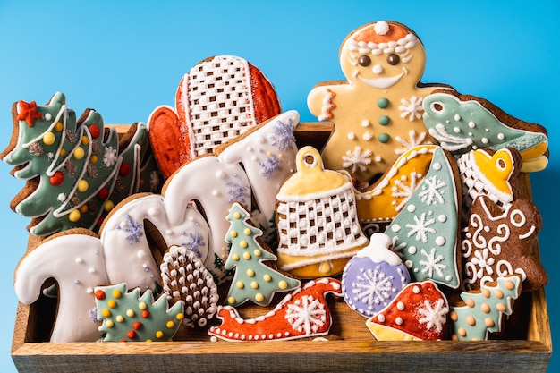 Christmas gingerbread in a wooden box on blue background.