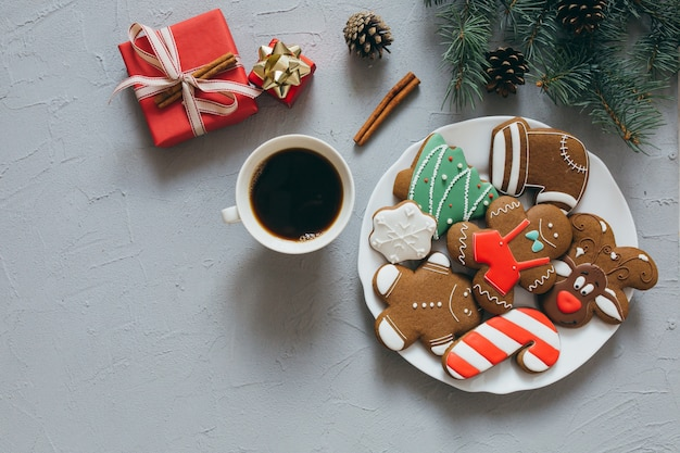 Christmas gingerbreads, and a cup of coffee on a gray background.