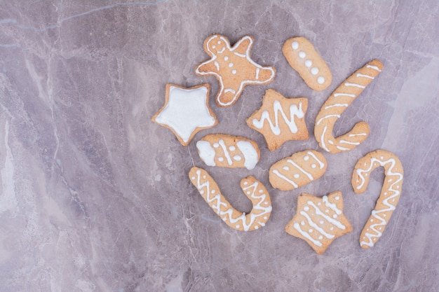 Christmas gingerbreads in different shapes on stone surface