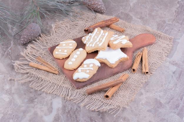 Pan di zenzero di natale in ovale e forme a stella su una tavola di legno con bastoncini di cannella intorno