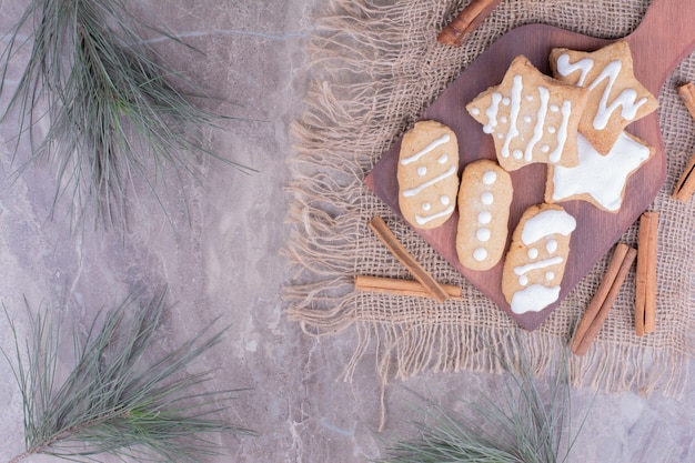 Christmas gingerbreads in ovale and star shapes on a wooden board with cinnamon sticks around