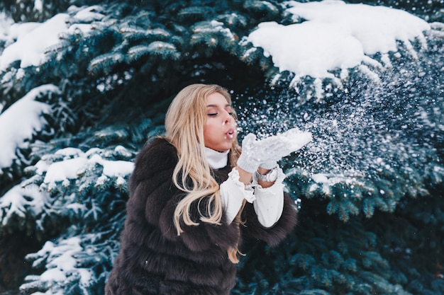 Christmas girl outdoor portrait, beautiful woman blowing snow in winter forest