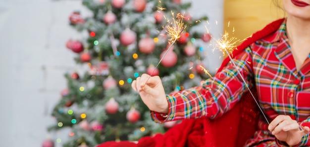 Рождество, девушка с бенгальские огни в руках. выборочный фокус.