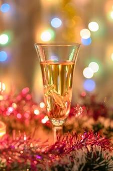きらめく花輪を背景にライラックの見掛け倒しに囲まれたスパークリングワインのクリスマスグラス。