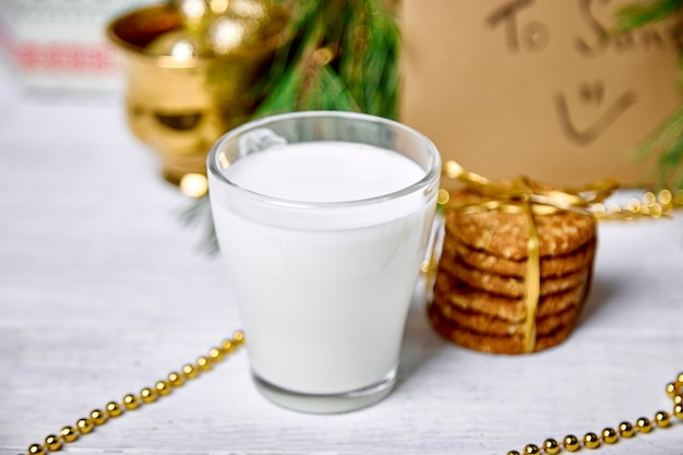 テーブルの上に牛乳とクッキーとクリスマスグラス