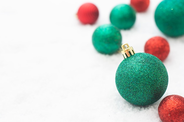 Christmas glittered green and red baubles isolated on snow. winter greeting card.