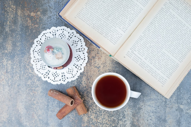 Christmas globe, cup of tea and open book on marble surface. high quality photo