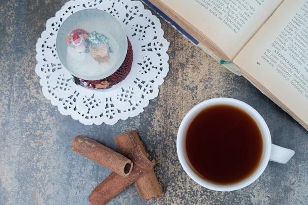 Globo di natale, tazza di tè e libro aperto sulla superficie in marmo. foto di alta qualità