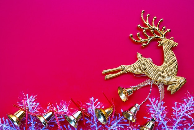 Christmas gloden reindeer and bell on red background. flat lay, top view, copy space