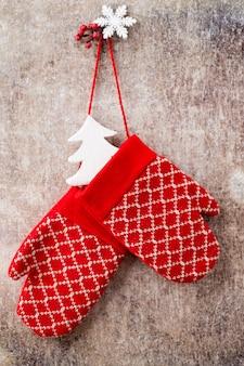Рождественские перчатки на фоне деревянной подарочной карты.