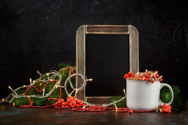 Christmas glowing garland in cup, chalk board, fir branches and rowan berries on dark