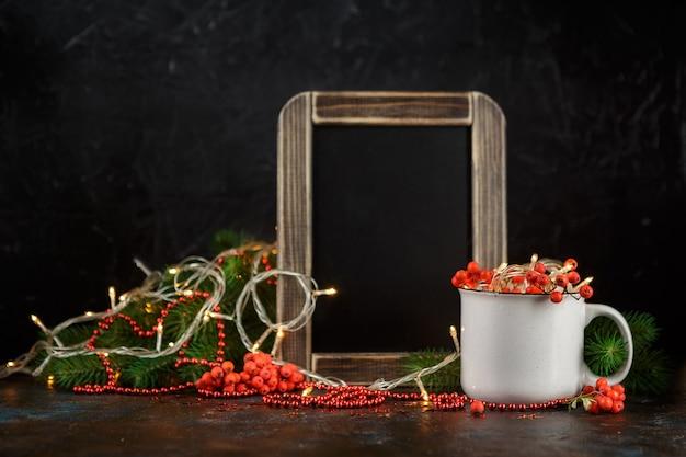 カップ、チョークボード、モミの枝、暗闇の中でナナカマドの果実のクリスマスの輝く花輪