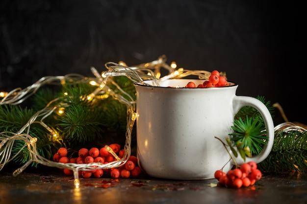 暗闇の中でカップ、トウヒの枝とナナカマドの果実のクリスマスの輝く花輪