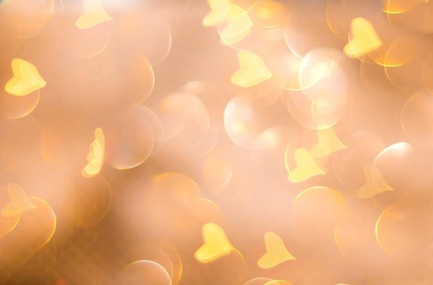 クリスマスの輝く黄金の背景。クリスマスのあかり。ゴールドホリデー新年抽象的なキラキラの焦点がぼけた背景、点滅する星と火花。ぼやけたボケ