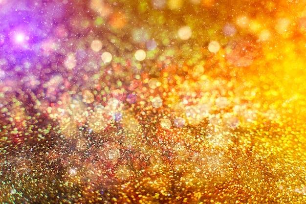Рождественский светящийся золотой фон. рождественские огни. золотой праздник новый год абстрактный блеск расфокусированным фон с мигающими звездами и искрами.
