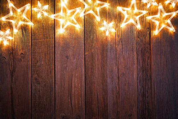 Christmas glowing stars on vintage wood
