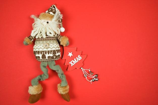 Рождественский гном-игрушка на красной поверхности с символом рождественской елки