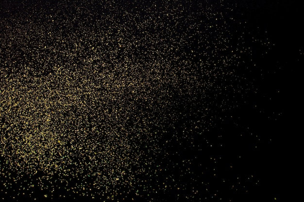Christmas gold glitter on black background. holiday abstract texture