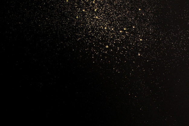 Christmas gold glitter on black background. holiday abstract