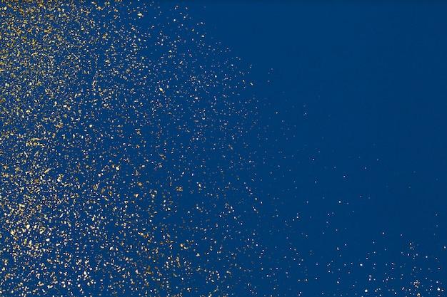 Рождество золотой глиттер на синем фоне. праздник абстрактных текстур