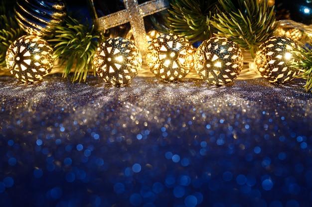 Рождественское золотое освещение на синем блестящем столе с деревом и украшением