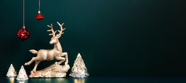 ダークブルーグリーンの背景にぶら下がっている赤いつまらないクリスマスツリーランプライトとクリスマスゴールドトナカイ。デザインの表示のためのバナーモックアップまたは休日のイベントの招待状