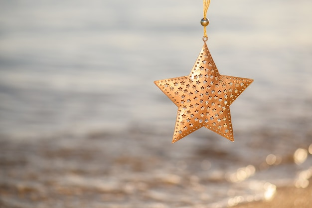 Christmas gold star decoration on the beach