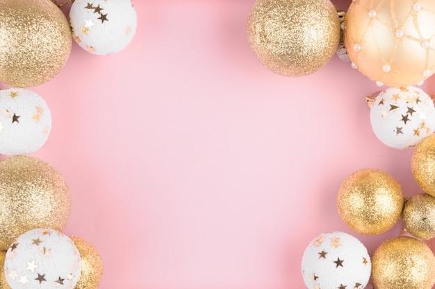 スタイリッシュなピンクのお祭りのエレガントな背景にクリスマスの金色と白のボールフレーム