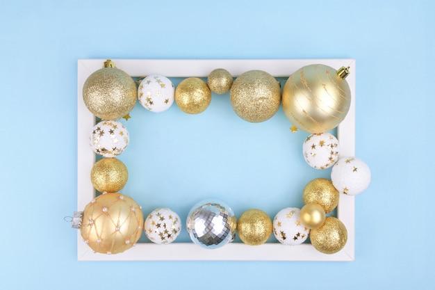 Рождественские золотые и белые шары в фоторамке на синем праздничном элегантном фоне