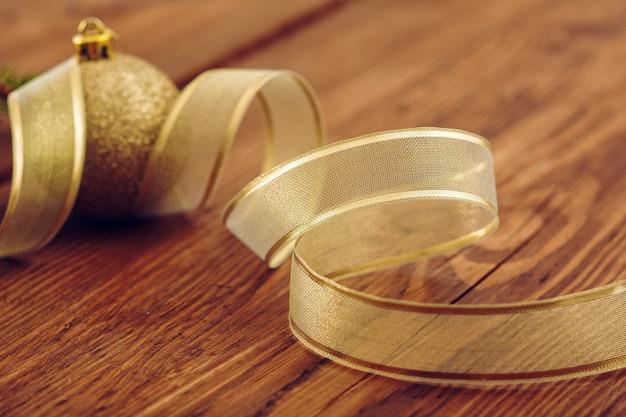 나무 배경에 노란색 리본 나선 가운데 크리스마스 황금 공