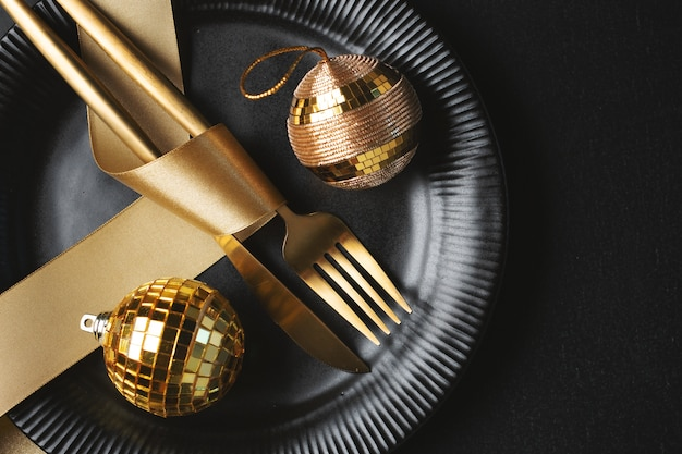 Christmas golden cutlery on plate with bauble and ribbon on black. flat lay.