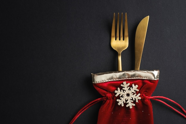 Christmas golden cutlery in small textile bag with snowflake and ribbon on black. flat lay.