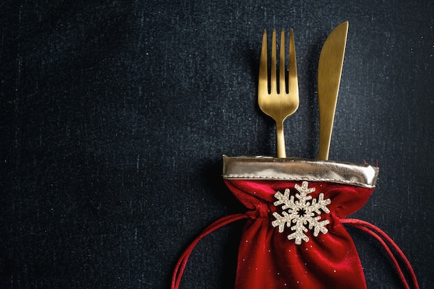 Christmas golden cutlery in small textile bag with snowflake and ribbon on dark background.